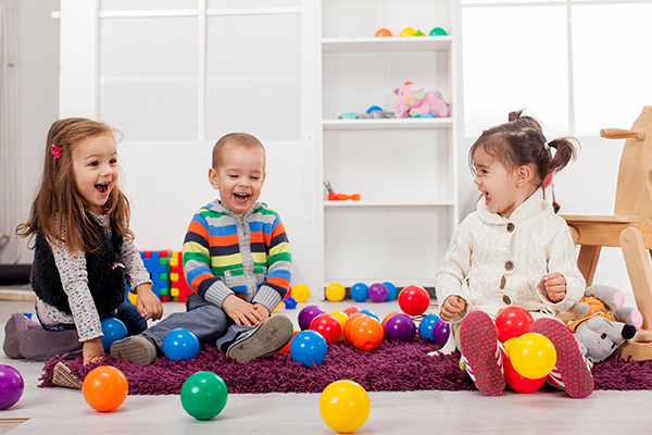Three small children sitting on the floor playing with brightly colored balls