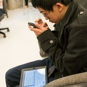 young boy holding iphone close with tablet on his lap
