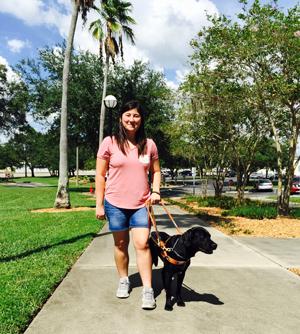 Michelle walking down campus sidewalk with dog guide