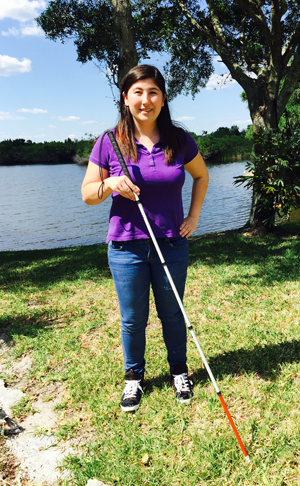Michelle as a teenager, standing by a lake with white cane