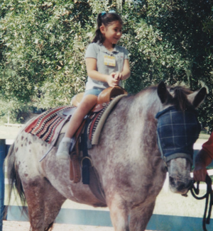 A young Michelle sitting atop a horse