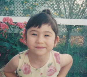A young Michelle smiling directly at the camera