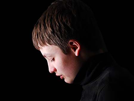 Teenage boy is photographed in profile on the black background. He is upset and his head is hung.