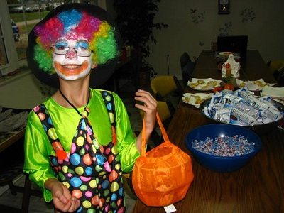 A kid dressed up as a clown for Halloween holding a bag for trick-or-treating