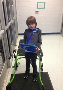 JD Bowdoin standing in front of the school door using his walker