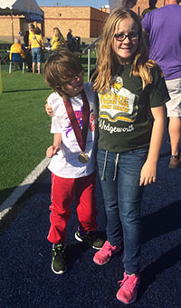 JD wearing his gold medal standing with his twin sister