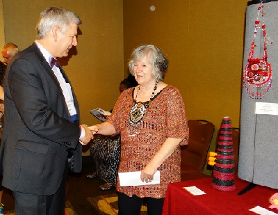 Lynda receiving award from president of APH with talisman pinned to board on far right