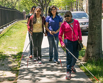 Young women walking with canes on the sidewalk