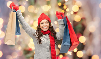 Happy young woman in winter clothes with shopping bags in front of a Christmas tree