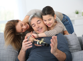Woman with daughter hugging a grandfather and giving him a present