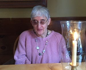 older woman wearing glasses and necklace, seated looking down