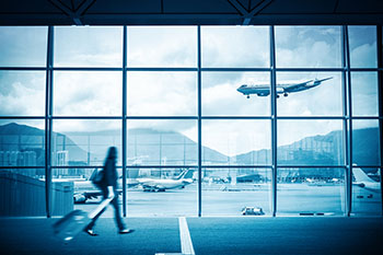 Modern airport scene of a passenger walking inside the airport looking outside through the large window
