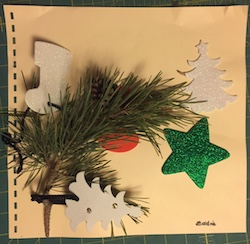A collection of cut outs in different shapes and an evergreen branch on braille paper
