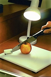 apple on cutting board with a gooseneck lamp