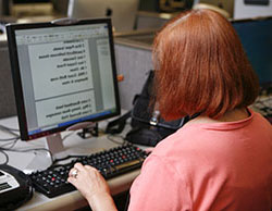 Woman sitting down looking at a computer screen with enlarged text