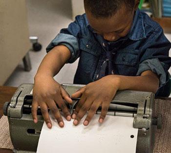boy leaning over braillewriter