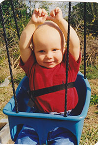 Jake at 18 months old sitting in a swing