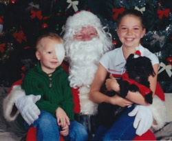 Jake with eye patch at toddler age with Santa