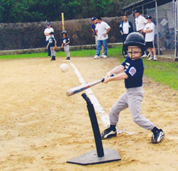 Jake at bat hitting a ball during a tee ball game