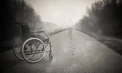 empty wheelchair in street with woman walking in distance