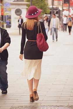 woman walking on street with back to camera, handbag hanging at side