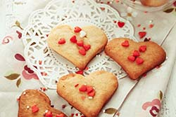 Heart-shaped cookies with red heart sprinkles