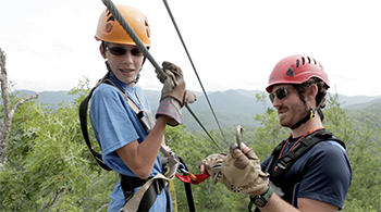 A camper getting hooked up to a zip line by an instructor