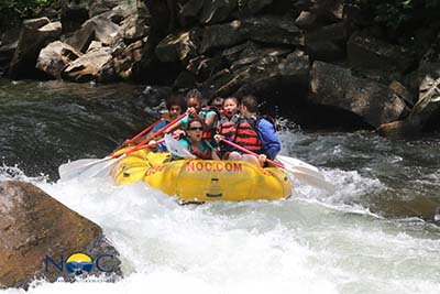 A group of campers and instructors white water rafting