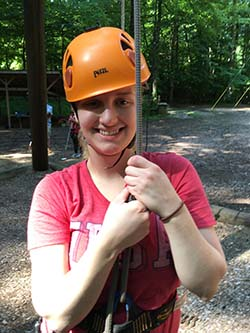 A camper in rock climbing gear smiling at the camera