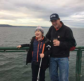 Eddie and his father standing in front of a fence on a ferry