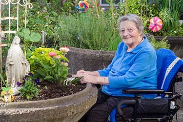 A woman in a wheelchair outside working in a raised garden