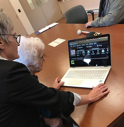 older woman using laptop to learn zoomtext with instructor looking over shoulder