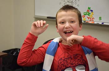 Eddie at school in a bright red shirt laughing with his hands in the air