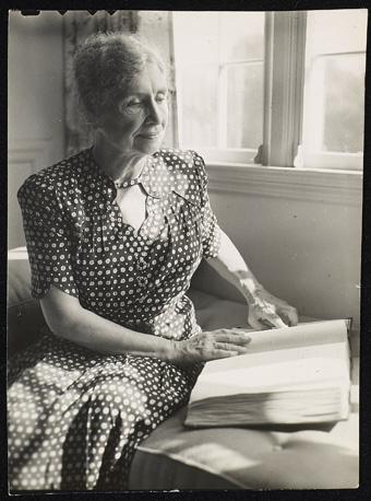 Helen Keller reading a book in braille
