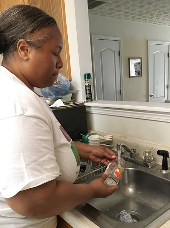 woman washing bottle in sink