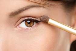 A close up of a woman applying eye makeup