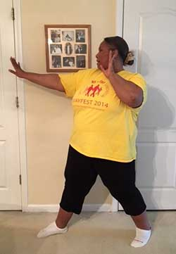 A side view of Empish demonstrating a self-defense stance with her feet apart and her hands up near her shoulders