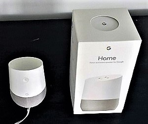 Google home device pictured next to packaging box for size perspective
