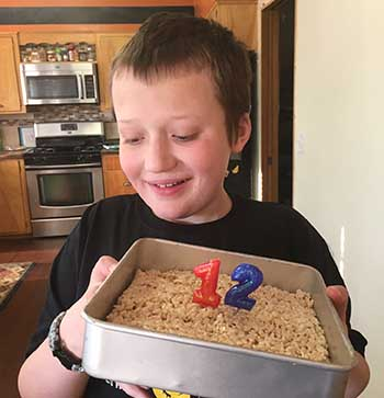 Eddie holding a cake in a pan with two candles on top for this 12th birthday
