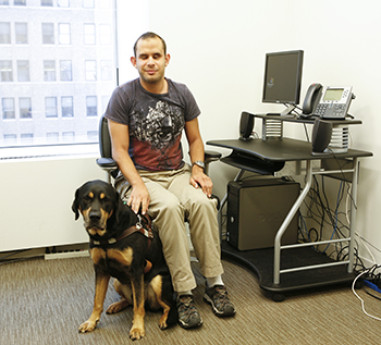 A man sitting at a desk with this guide dog looking at the camera