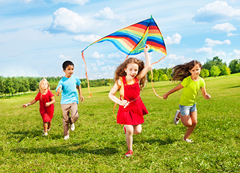 A group of kids running outside flying a kite