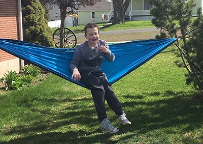 Eddie outside sitting in a hammock