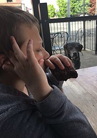 Eddie sitting outside at a table eating a brownie with a dog drooling over the food in the background