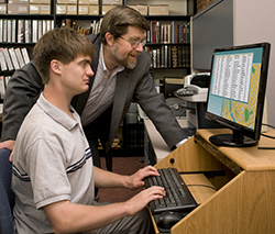 A male teacher standing behind a teenage student guiding them on using the computer