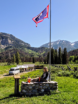 Emily Coleman sitting outside with her back against a flag pole in Jackson, Wyoming