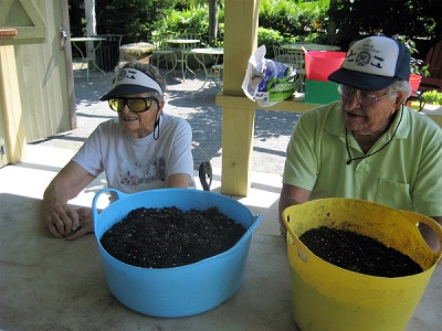 two boothbay support group members with pots in front