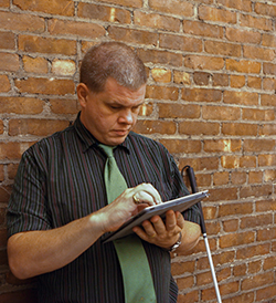 A man standing against a brick wall with his white cane using a tablet