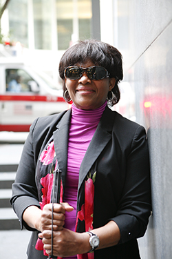 A woman standing outside with her white cane next to a building smiling at the camera