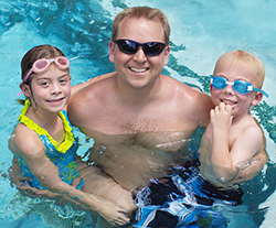 A father holding his two children in a swimming pool looking t the camera and smiling