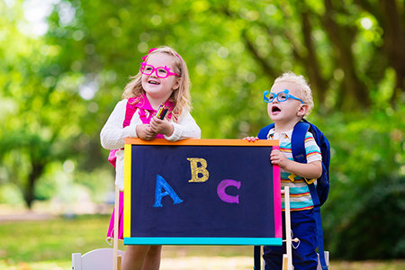 Two children with glasses wearing backpacks in front of a chalkboard with the letters A, B, and C